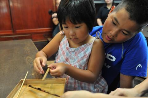 真剣な表情で箸に蒔絵を施すこ子供たち