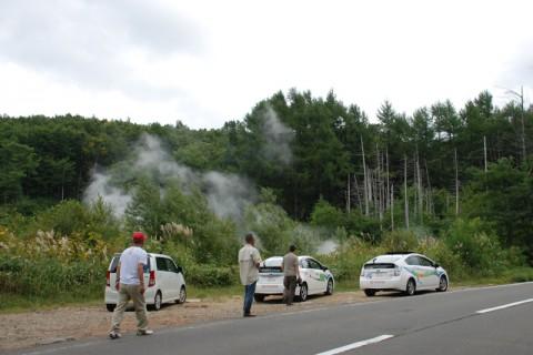 山腹の森林から蒸気が吹き上がる