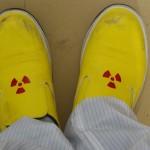 防護服を着て放射能マークのシューズに履き替える