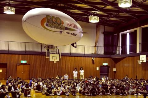 子供たちの頭上を飛ぶエコミッション号