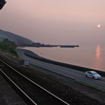 夕景の中を電車と走るプリウスPHV