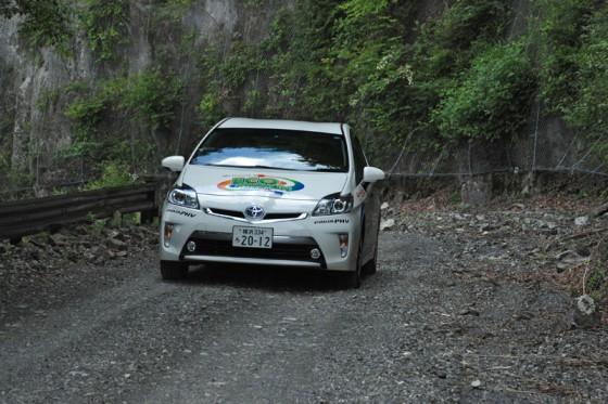 路肩に岩が転がる未舗装路を上るプリウスPHV