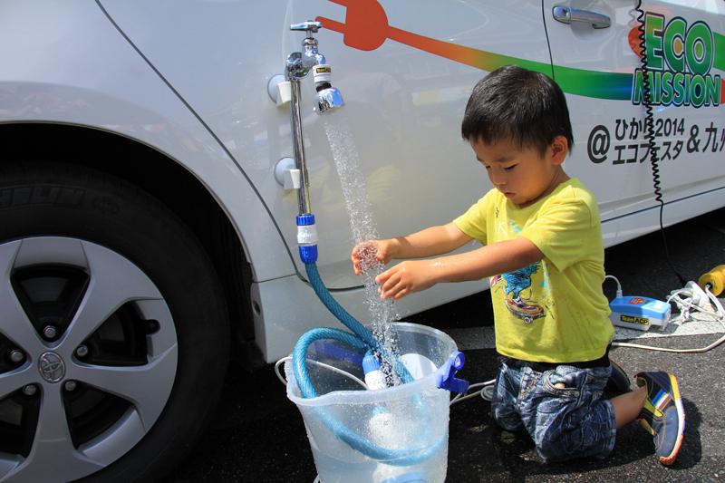 電動シャワーに夢中でびしょ濡れの男の子。晴天の暑い日で良かったね。