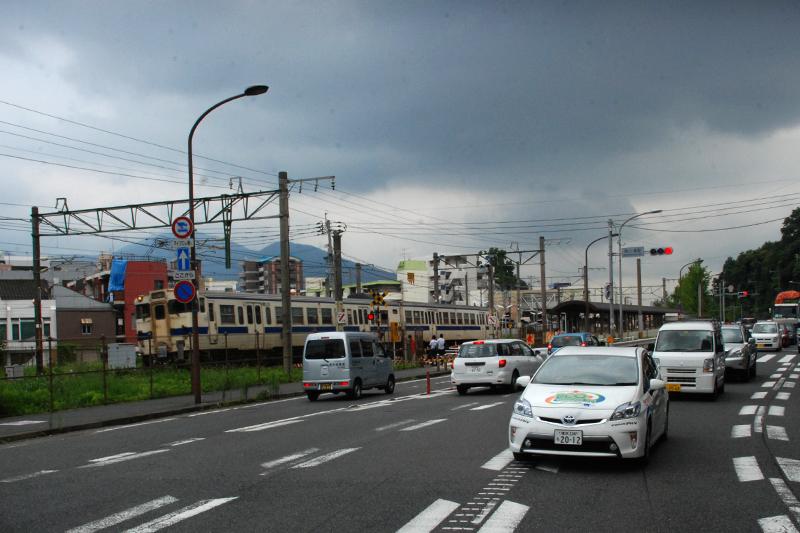日豊本線南小倉駅を出た415系と並走するプリウスPHV。