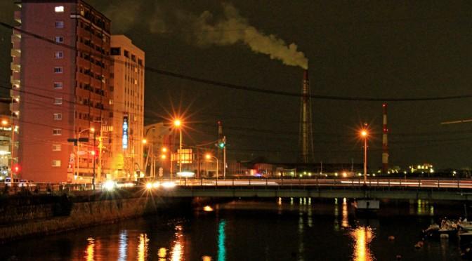 夜の関門港に聳える発電所の煙突。北九州は八幡製鉄所をはじめとする工業の街でもある。