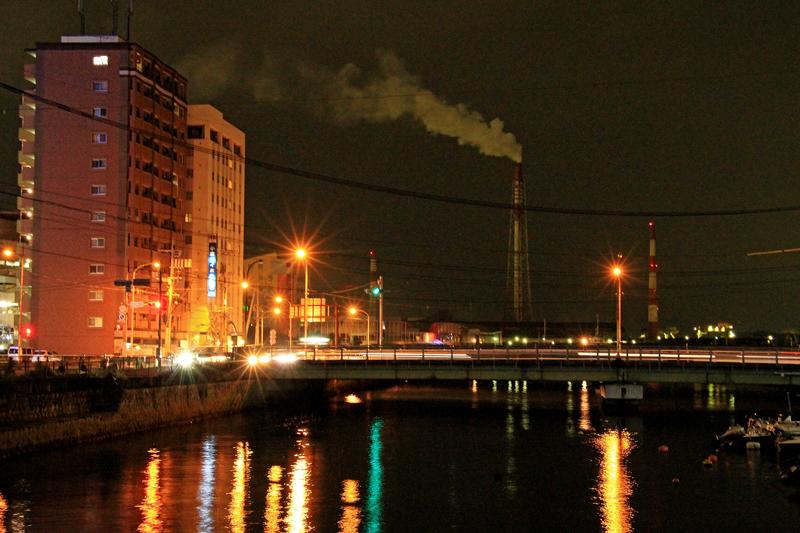 夜の関門港に聳える発電所の煙突。小倉は八幡製鉄所をはじめとする工業の街でもある。