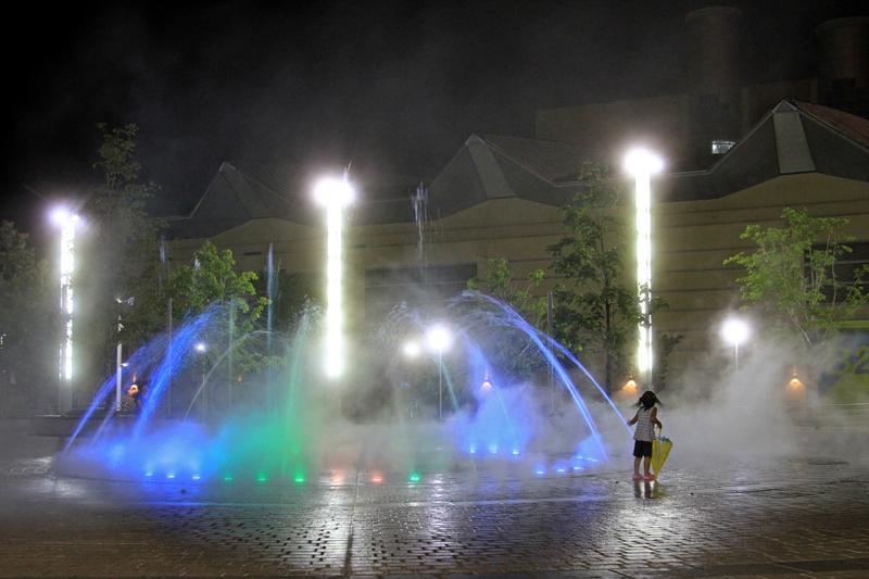 夜の公園で噴水と戯れる少女。