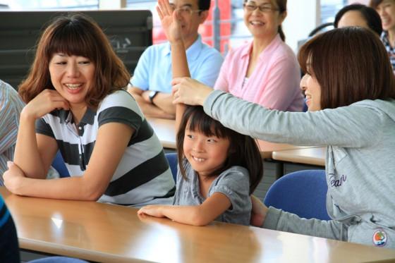 お母さんに手を支えられて挙げてクイズに答えるちょっとシャイな女の子。