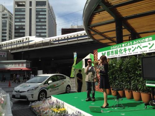 新幹線が間近を走る有楽町駅前広場でのトークショー。