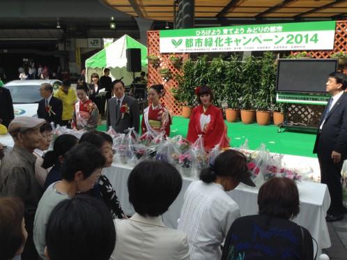 大臣と桜の女王が花鉢を手渡していました。